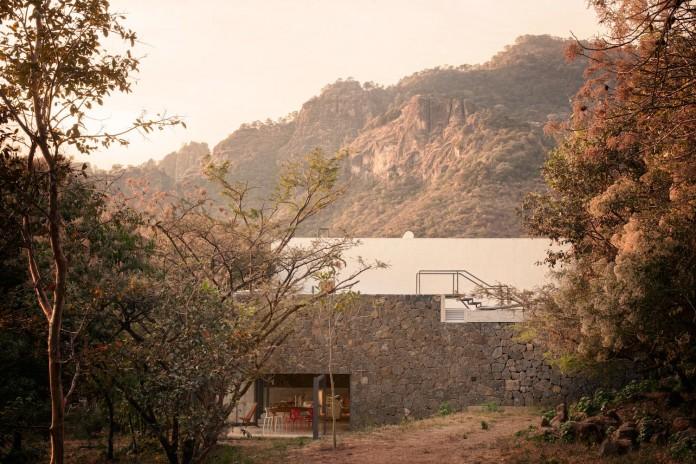 built-rough-stone-crawls-low-trees-casa-meztitla-edaa-15