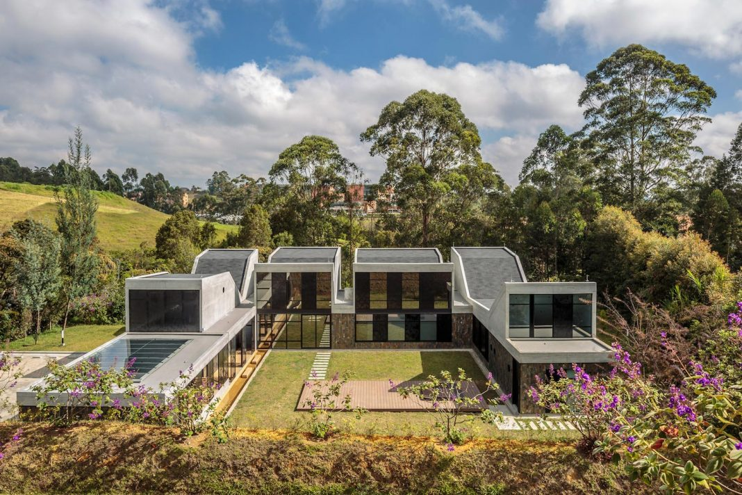 Plan B Arquitectos design VG House, a system of parallel concrete walls which define four volumes connected transversally