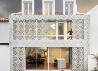 Restelo House with a rear made by a series of windows and shutters resembling a pattern of traditional Portuguese tiles by João Tiago Aguiar