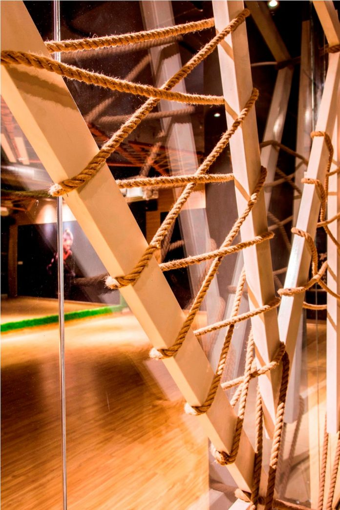 Moksha fitness and spa with overlapping and free standing triangular metal frames, crisscrossed with ropes, designed by Studio Ardete-14