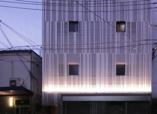Renovation of the 39 year old structure into contemporary building with a facade of white fins to conceal two stores