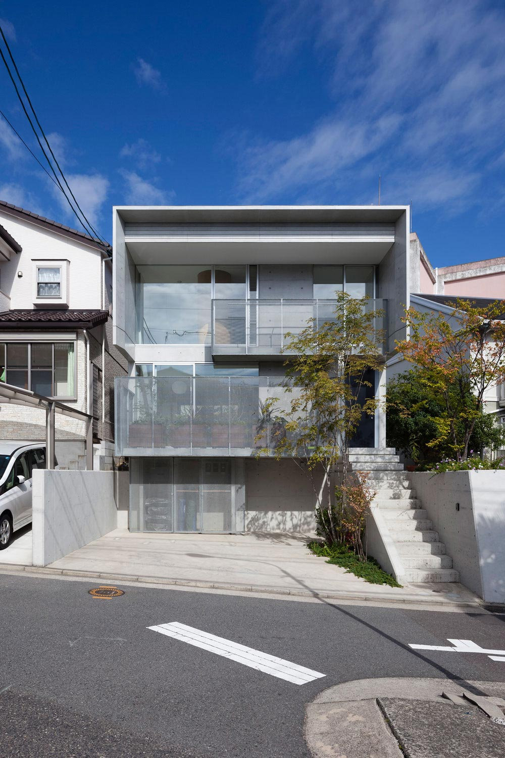 House in Midorigaoka: a triple tiered, nine-by-twenty two meters plot of land with a tuck under garage