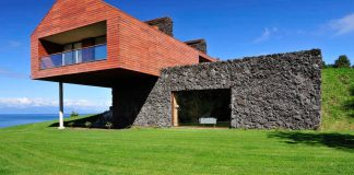 Maitén holiday residence situated on the shores of the Llanquihue Lake featuring wooden facades and red metal roofs
