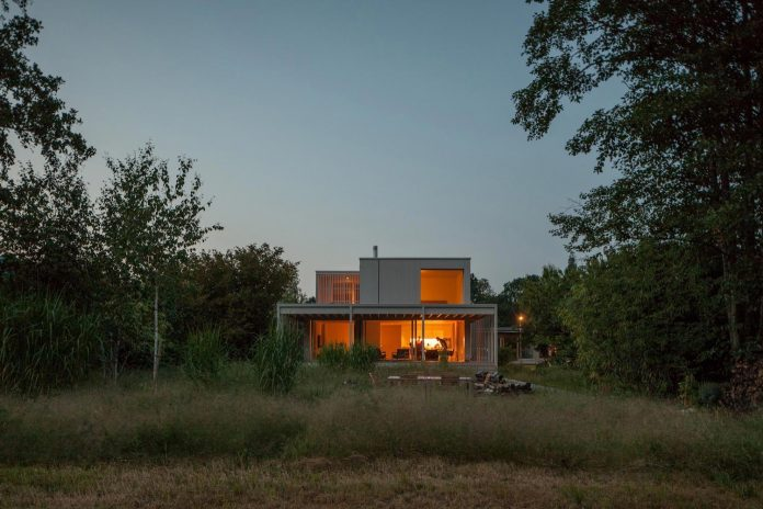 residence-keeps-strong-spatial-connection-surrounding-shore-zone-lake-biel-amidst-lush-vegetation-09