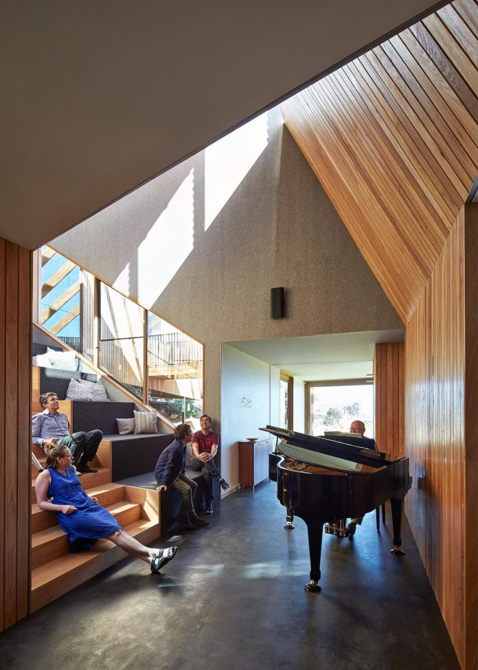 split-house-comprises-2-simple-volumes-linked-splayed-stair-used-seating-area-people-gather-06