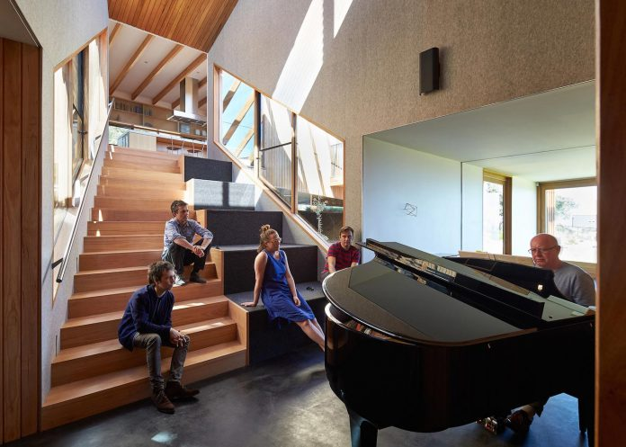 split-house-comprises-2-simple-volumes-linked-splayed-stair-used-seating-area-people-gather-07