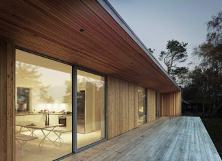 Wood and glass frame of a summer house surrounded by woods on Sweden's southern coast