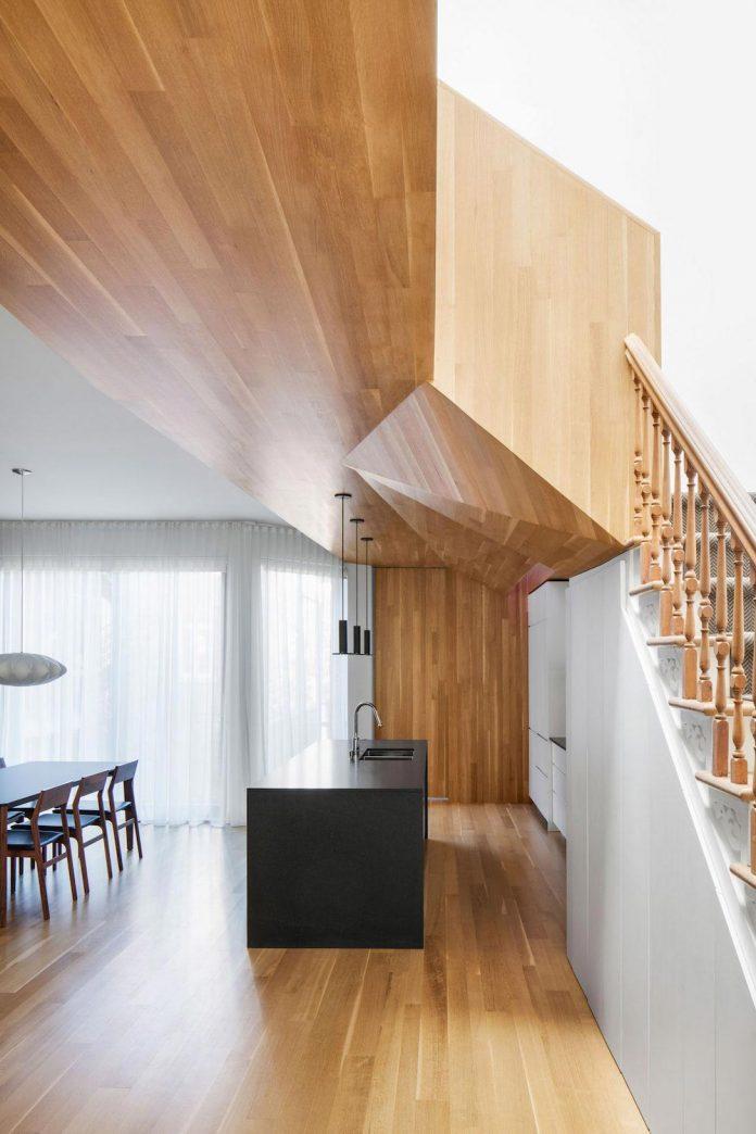duplex-facing-lafontaine-park-wood-surfaces-extend-continuously-space-07