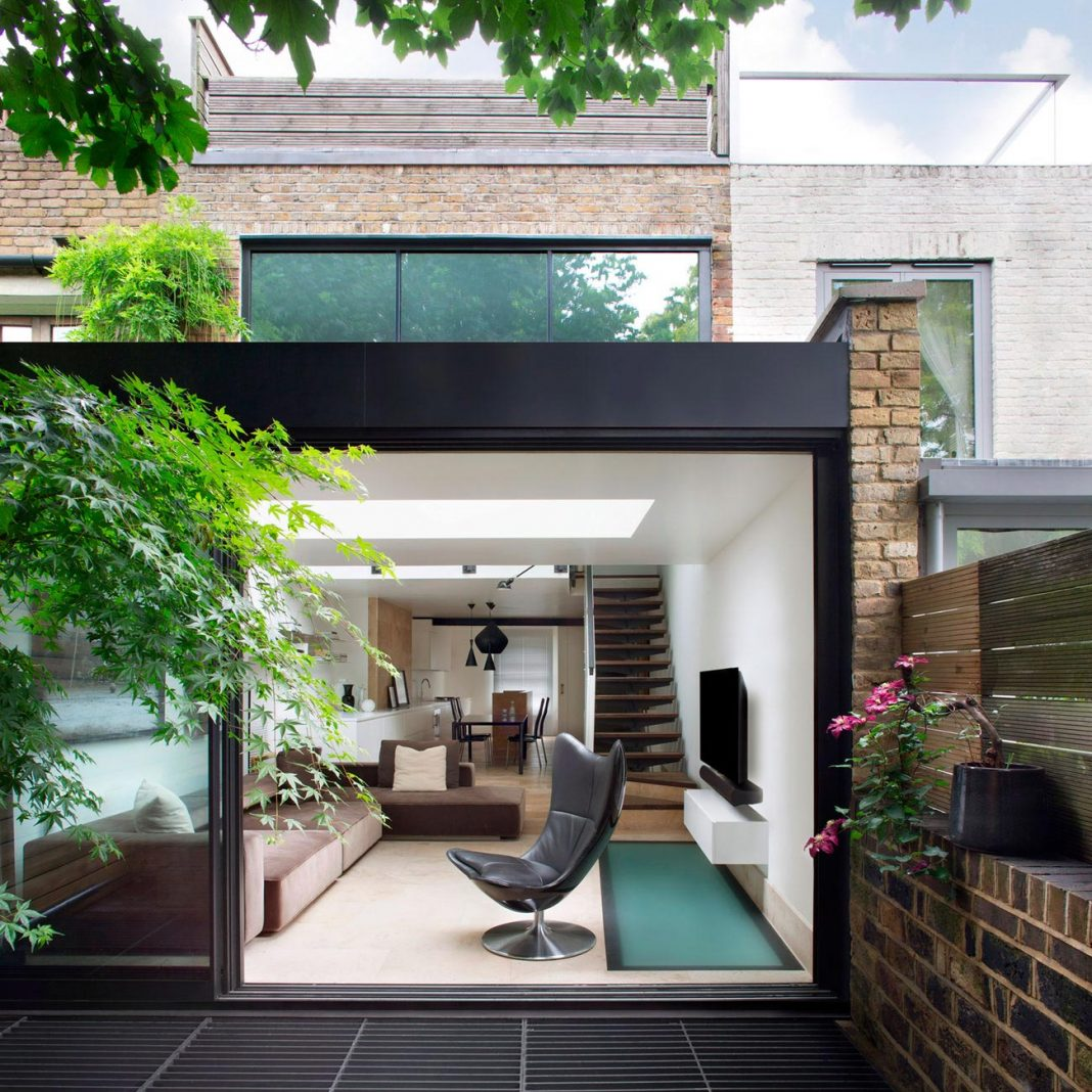 Brown brick family house contrasting modern sharp lines with vintage furniture
