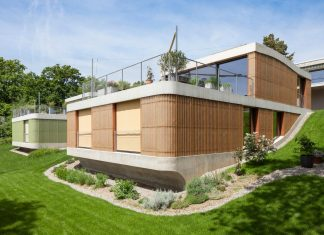 Curved shape of the roof connects the two floors and turns the location on a slope into a part of the design concept