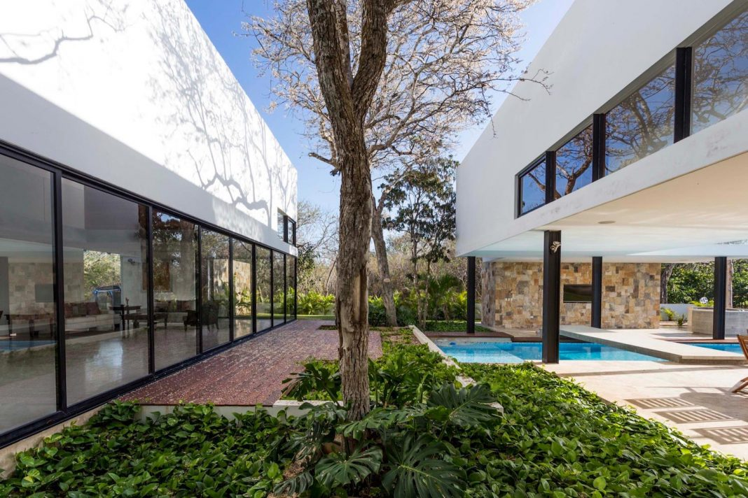 Irregularly shaped house surrounded by trees in an exclusive golf club development