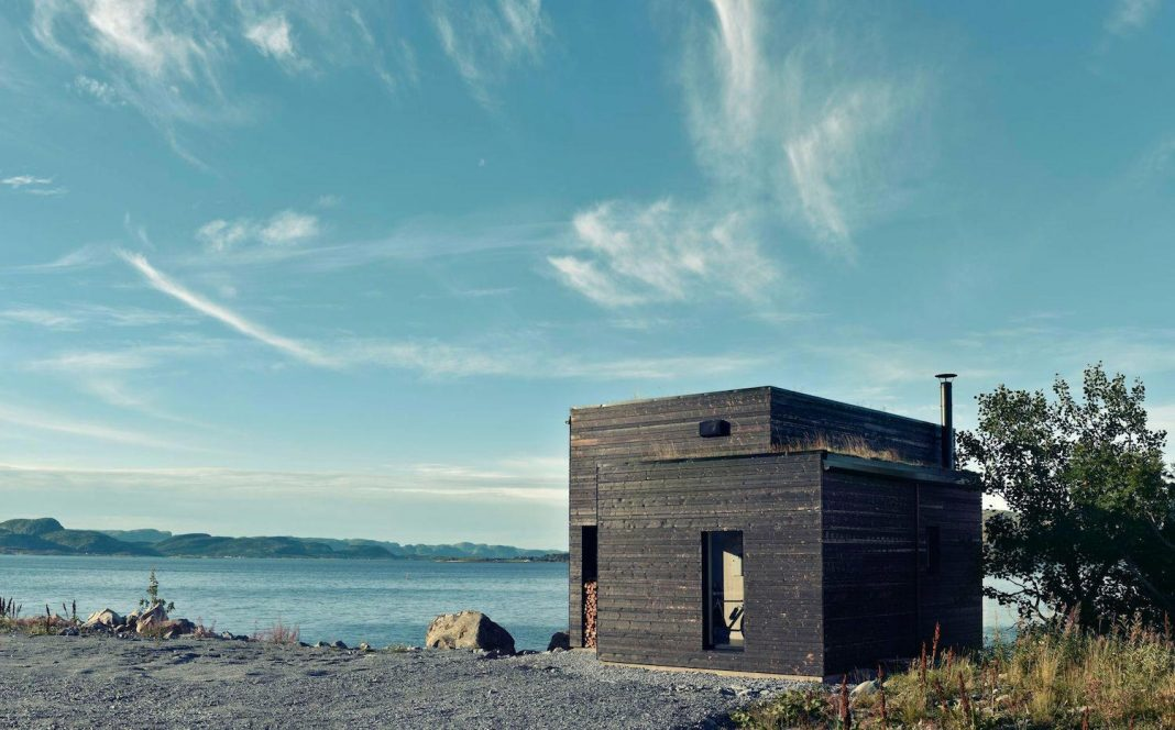 Small wood house on the coast of Norway, just next to the water