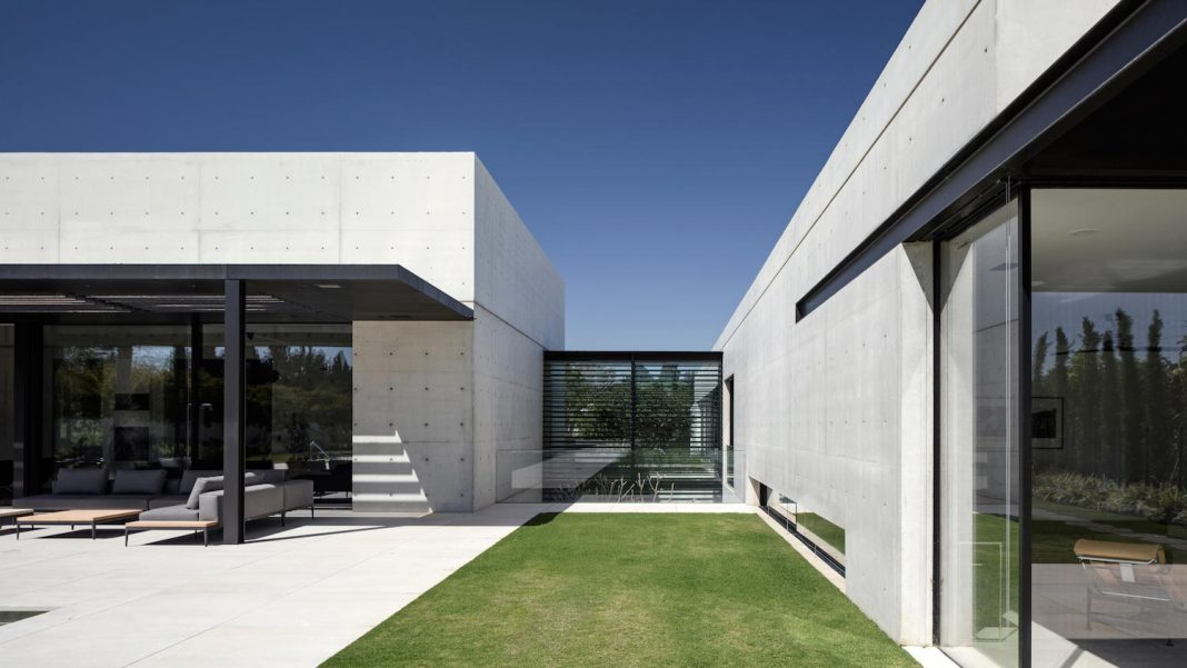 minimalist concrete and glass house consists of two