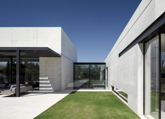 Minimalist concrete and glass house consists of two volumes connected by an glazed corridor
