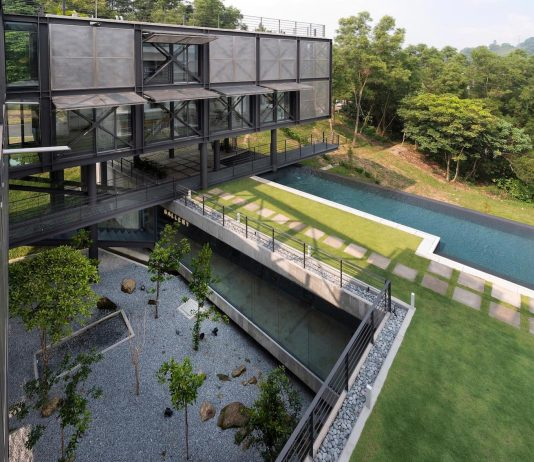 Exposed structural steel house is designed to 'float' over the site offering spectacular rainforest views