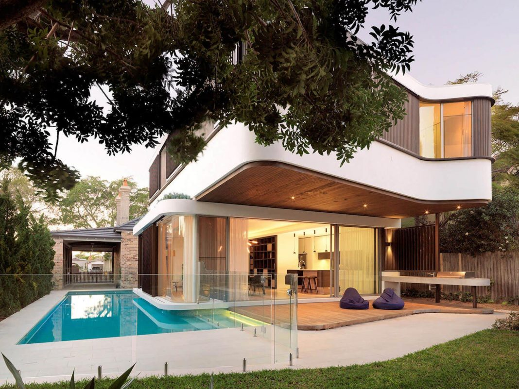 Pool house addition at the back of a single storey 1910 cottage is surrounded by a swimming pool