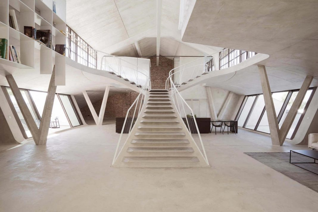 Rounded concrete staircase opens up all rooms and also appears to be carrying them