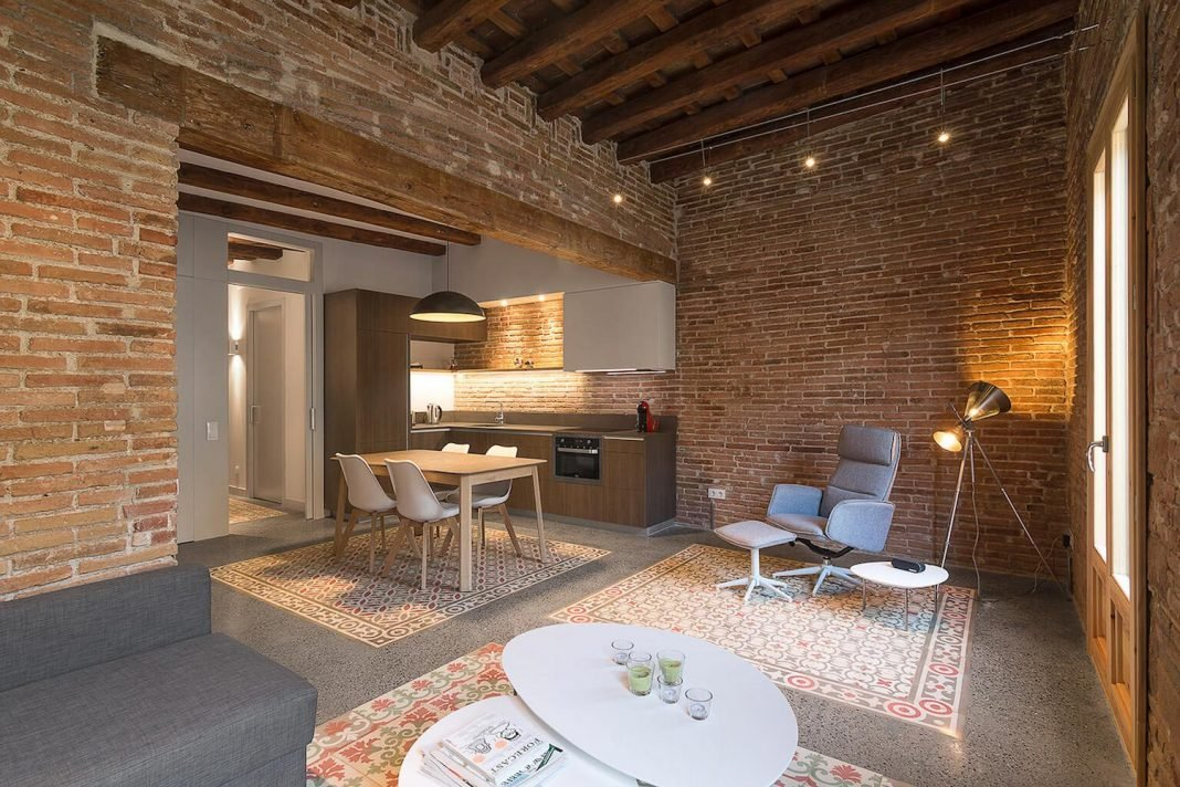 Contemporary flat in Barcelona's Eixample defined by the Catalan hydraulic cement tiles and exposed brick walls and the wooden beamed ceilings