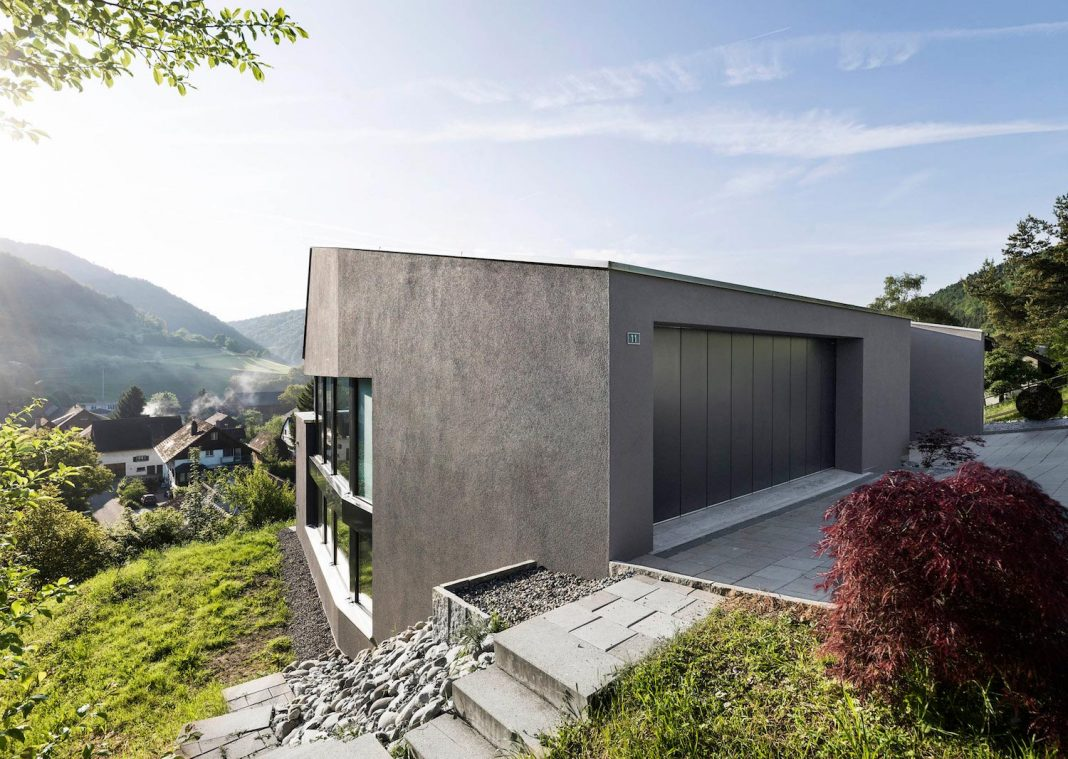 Single family house built on a steep slope that leads to for Home built house