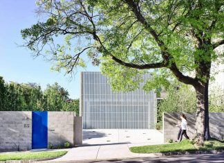 Moving House: White aluminium screen forms a singular mass in the outline of a suburban gable roof