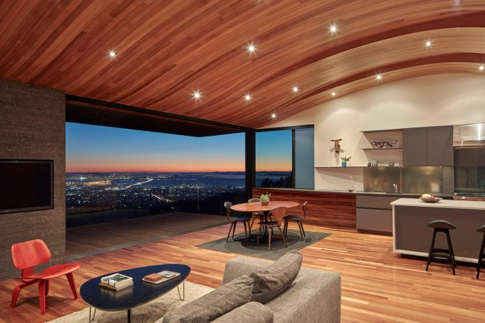 Contemporary conversion of an fire-storm house into a modern home with a curved wood ceiling
