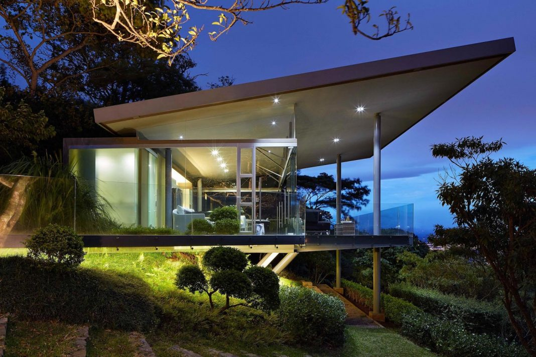 glass house elevated on top of metallic columns has also 3 big glass sides that create home design