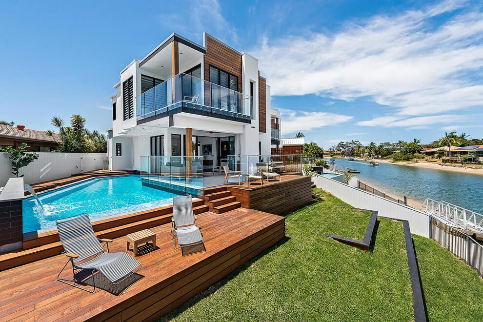 Modern home design in Broadbeach Waters with a contrasting interior between white, natural wood and black