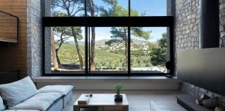 Amazing house with its facades completely open up through large glazing to the view of the pines trees