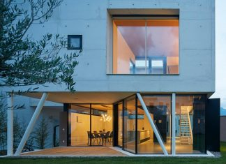 Concrete house uses old walls to create private patio allowing to add full glass walls to the residence