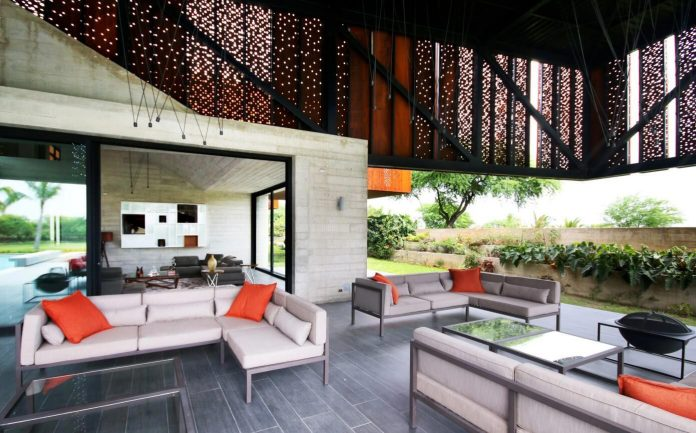 Exposed concrete for the first floor and a second floor covered in Corten steel panels with different size perforations