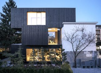 Extension and renovation that adds 3 new rectangular volumes covered in dark woodby Ofis Arhitekti