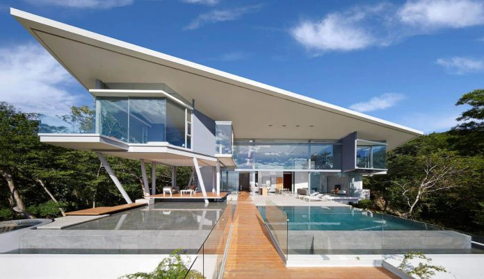 Modern house situated on a slightly downward sloping ridge of a peninsular shaped lot with forest on both sides