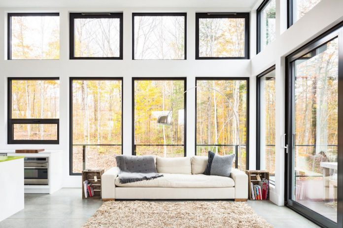 the main floor boasts primarily white furnishings accented with natural wooden and sandy tones that complement the natural forest outside - Structure Of Home Design