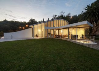 Particular design of a house using white concrete wall that protects it replaced on the South side by a glazed closure