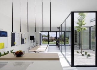 Single family house open to the garden and the courtyard having a simple, white design and limited amount of materials