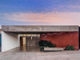 House with the leaning red wall which directs the perspective to the beginning of the journey