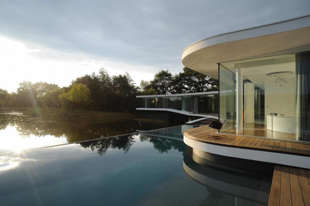 House mainly built with raw materials with its swimming pool immersed in the lake