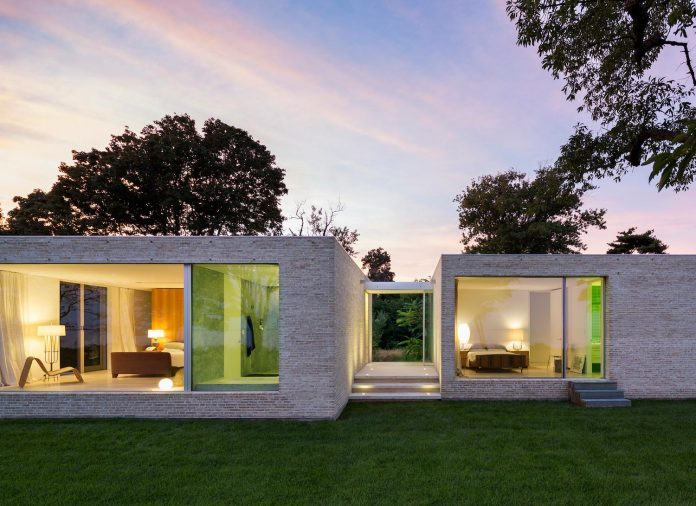 Weekend home built on the south shore of Long Island having large sliding glass doors to experience the landscape around the house