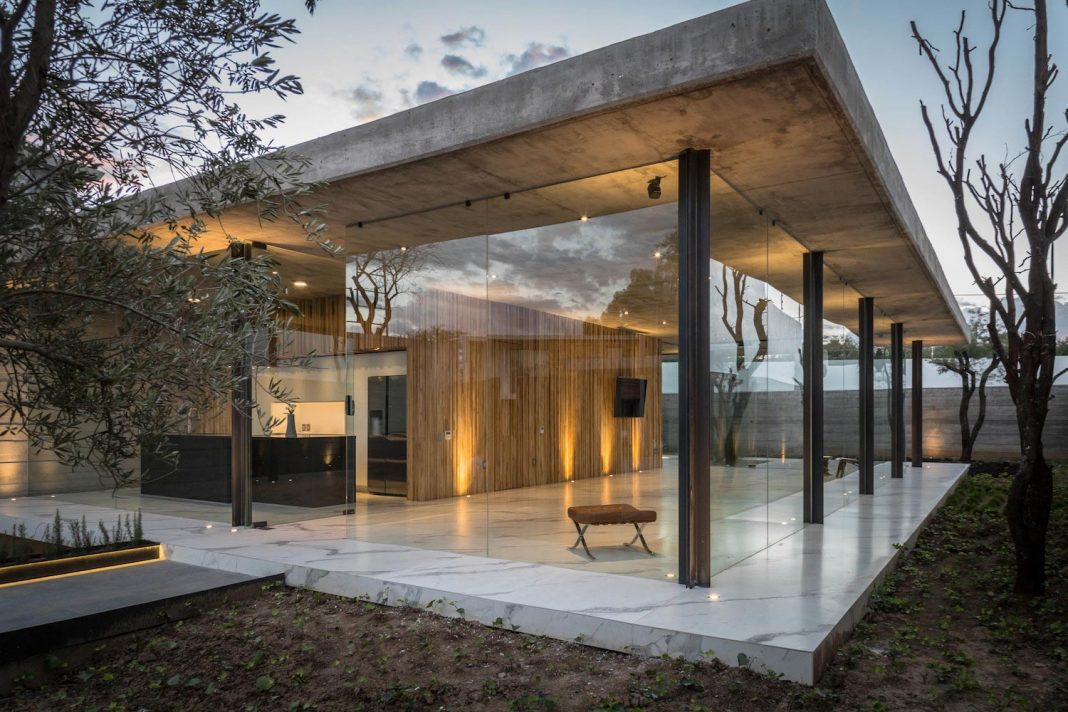 House which manifests its character with an apparent concrete wall and with wooden access doors