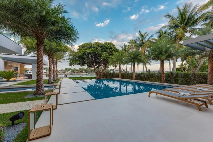 the wide open yard boasts an oversized infinity edge pool that flows into shallow water and becomes a reflecting pond wrapping around an island with - Tropical Apartment Design
