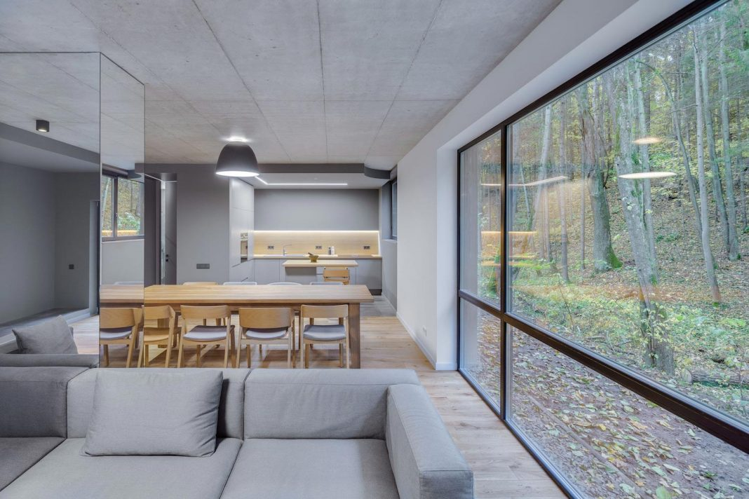 A house recessed and hidden behind a continuous concrete wall by YCL studio